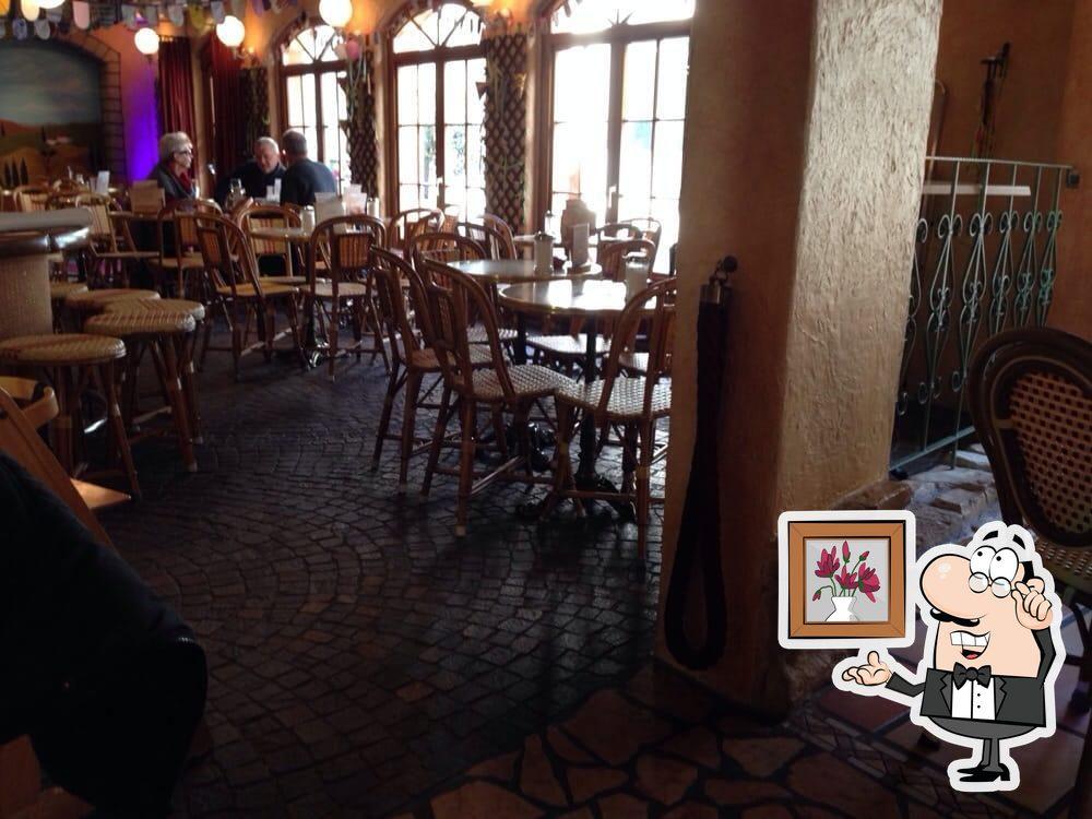Nehmt an einem der Tische im Cappuccino - Café-Bistro-Cocktailbar Platz